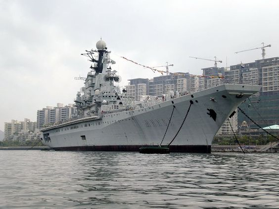 The starboard side of the former Soviet aircraft carrier Minsk moored in Shenzhen, China, as seen from a motorboat that can be rented for a 5 minute cruise around the starboard and bow of the Minsk. The Minsk is the centerpiece of the Minsk World military theme park.    © BrokenSphere / Wikimedia Commons.