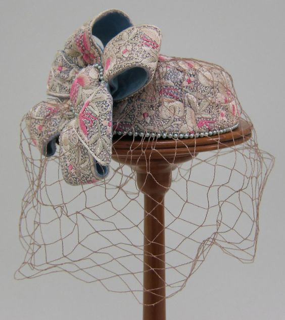 Off-white and pink brocade pillbox hat with light tan veil | Designer: Benjamin B. Green-Field (Bes-Ben) | United States, 1955 | The conical crown with flattened top is made of brocade fabric with flowers and butterflies | On the right side of the hat is a large bow made of strips of the brocade backed in a gray/blue | The center of the bow is encircled with a band of gray beads, with a matching band of beads at base of hat | University of North Texas