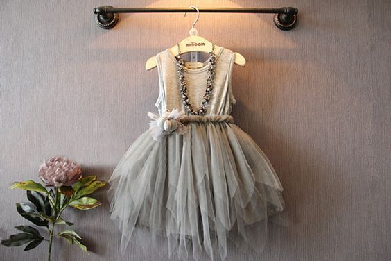 Glam! This dress has it all- a full tulle skirt and an adorable removable floral pin at the waist. Perfect for any special occassion or even as a flower girl dress.
