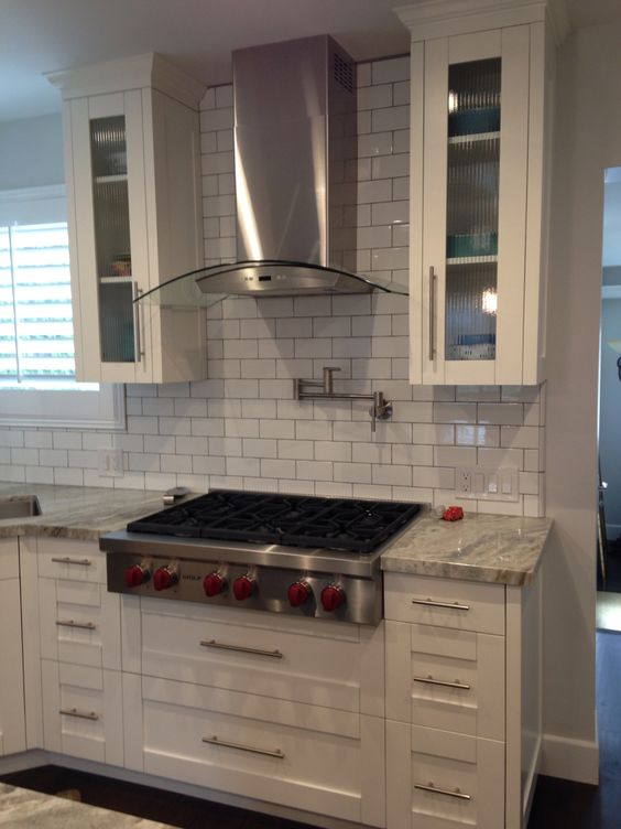 Exhaust hood pot filler faucet and white shaker cabinets for Shaker style kitchen hoods
