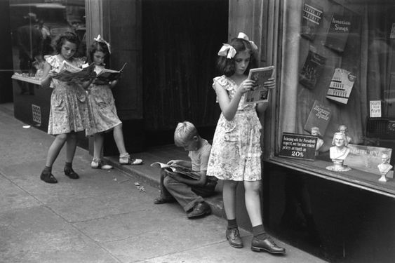 1947, Four children reading comics by a store display window, New York City. Photo by Ruth Orkin