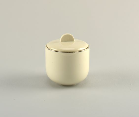 Creamy-grey porcelain body. (a) sugar bowl milk jug is cylindrical in shape, with curved lower section that tapers to circular foot. (b) cover is slightly domed, with flat semi-ciruclar upright finial. Platinum band painted around lip and spout.
