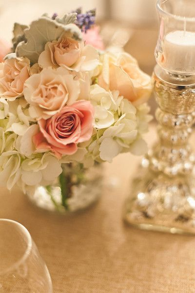 soft mixes of flowers and mercury glass on burlap gives this table a mix of vintage and rustic