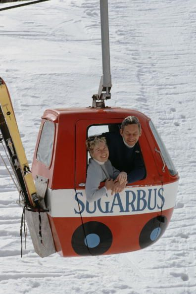 Snow Lift. Slim Aarons.   March 1969: Damon Gadd founder of Sugarbush ski resort, Vermont with his wife in a 'Sugarbus' snow gondola.: