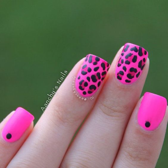 Leopard print nail art design in hot pink nail polish. Use black polish to detail the leopard prints as well as a darker pink polish for the additional leopard print details.