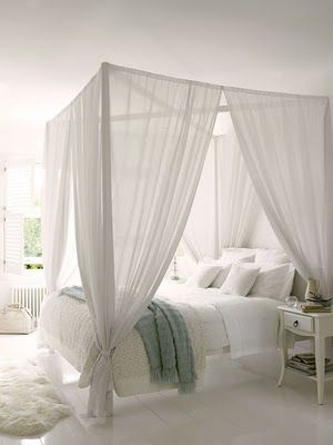 White bedroom with a four poster bed.