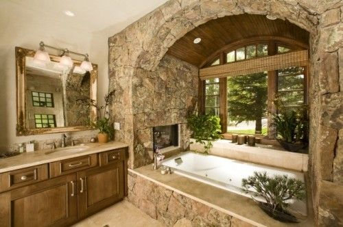 love the stone and fireplace in this bathroom