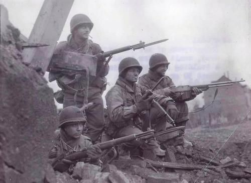 American soldiers during the Battle for the Ardennes. *note the soldier carrying a BAR on extreme right, then the M3 Grease Gun next to him.