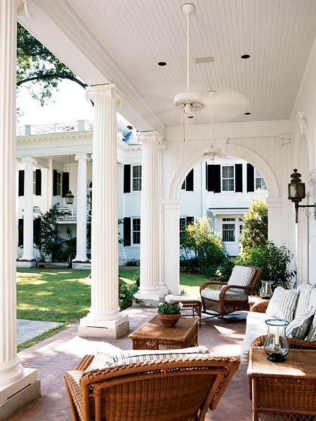Southern-style outdoor living. Loving this plantation style home with wraparound outdoor living space.