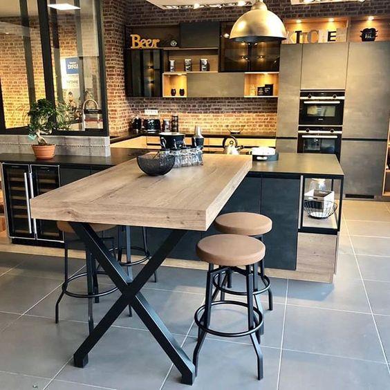Une table industriel, un mur en brique, une cave à vin encastrée et des meubles acier et bois pour une cuisine noire et bois réussie