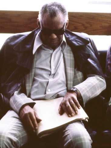 """Ray Charles Reading Braille.  (September 23, 1930 - June 10, 2004) known by his stage name Ray Charles, was an American pianist and musician who shaped the sound of rhythm and blues. He brought a soulful sound to country music, pop standards, and a rendition of """"America the Beautiful"""" that Ed Bradley of 60 Minutes called the """"definitive version of the song, an American anthem."""
