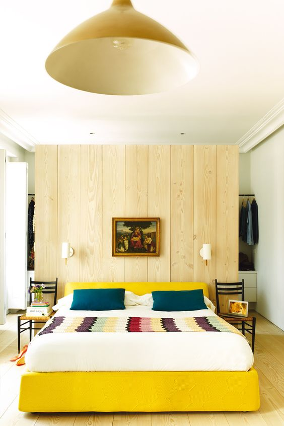 yellow bed, wood accent wall