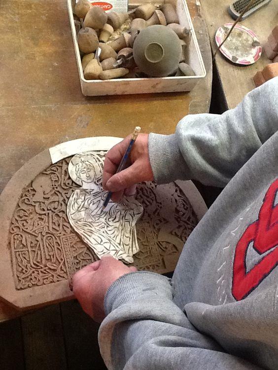 Styopa pencils the design onto the stone