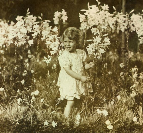 Princess Elizabeth II stands in a field of flowers, in this photo lovingly taken by her father, King George VI, in 1930.