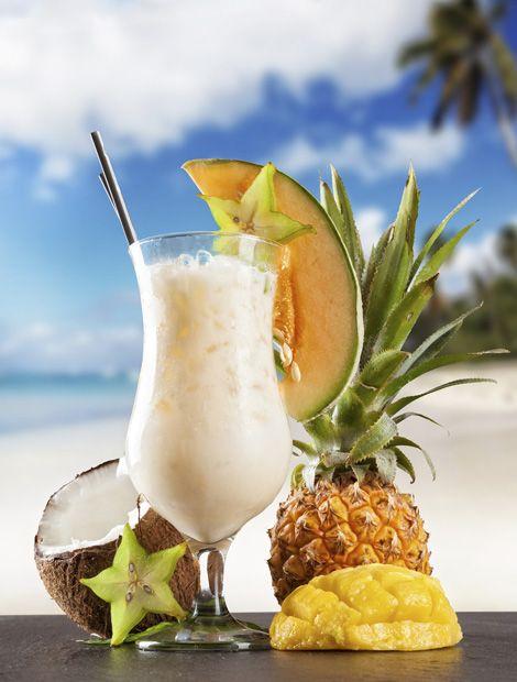 Pina Colada       Zutaten: 2 cl weißer Rum, 2 cl brauner Rum, 2 cl Kokossirup, 2 cl Sahne, 8 cl Ananassaft, 1 Ananasscheibe zum Dekorieren. Zubereitung: Alle Zutaten mit Eis im Shaker mixen und in das vorgekühle Glas seihen. Nach Geschmack etwas Eis hinzu geben. Deko hinzufügen. (Rezept & Foto: iStock/Jag_cz)
