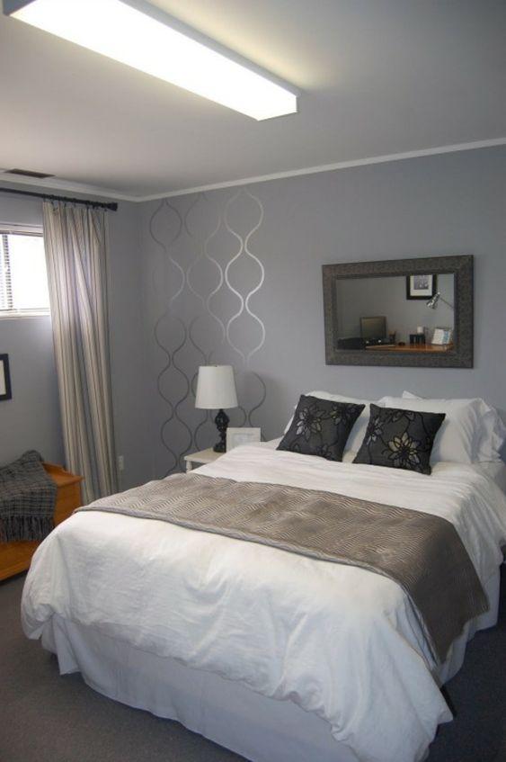 schlafzimmer mit einem großen bett, graue wand und interessante ...