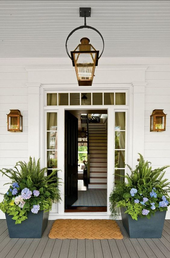 Large planters with blue hydrangea, ferns, and ivy flank a front door and create symmetry on the charming porch. #frontdoor #curbappeal #porch #decoratingideas #hydrangea