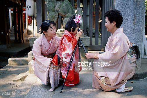 Japan, mother, daughter (4-6) and grandmother at Shinto shrine