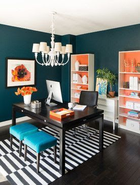 Deep turquoise walls, storage unit with backs painted vibrant orange, anchored with black desk and black and white striped rug