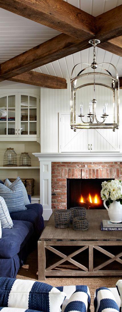 Strandhaus Stil mit gemütlichem Kamin und frischen Blumen. Die blau weißen Sofas und Kissen sorgen für einen nordischen Touch.