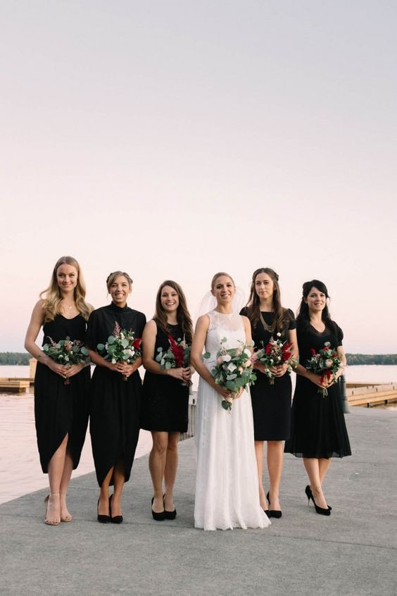 Mismatched black bridesmaid dresses and pretty pops of maroon in the leafy bouquets | Image by Micheal Beaulieu: