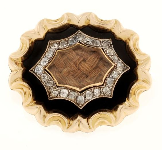 A mid Victorian gold, enamel and diamond mourning brooch, circa 1870, the central cartouche shaped glazed locket within a surround of cushion shaped old cut diamonds above a black enamel border and gold scalloped edge, 3.1cm long