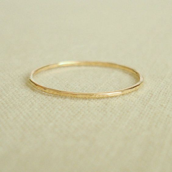 One tiny gold stack ring (Kristen Wiig wore this style of skinny rings as first knuckle rings on Bridesmaids)