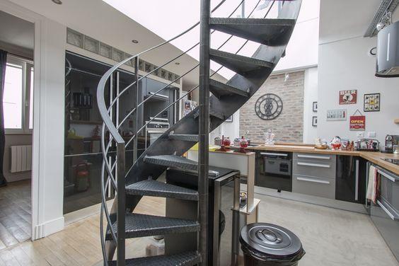 Espaces Atypiques Paris : Dernier étage avec toit terrasse proche Champs Elysées. Escalier hélicoïdal pour accès terrasse an acier avec marches en tôle striée réalisé par Escaliers Décors® (www.ed-ei.fr).