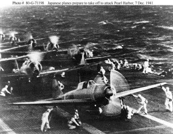 "Prelude to War: Japanese Strike Force Takes Aim at Pearl Harbor - Japanese naval aircraft prepare to take off from an aircraft carrier (reportedly Shokaku) to attack Pearl Harbor during the morning of 7 December 1941. Plane in the foreground is a ""Zero"" Fighter. This is probably the launch of the second attack wave. The original photograph was captured on Attu in 1943. Official U.S. Navy Photograph, National Archives Collection."