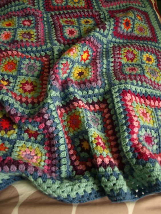 I love how the small squares are grouped in clusters and bordered before joining into the blanket.: