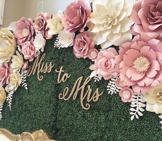 "Here's a close up picture of the beautiful paper flower backdrop I installed this past weekend.  For those of you who asked, the backdrop is a faux boxwood hedge wall rented from a local rental company.  Since the hedge wall had grids (you can see it up close) on them I used ""S"" shaped metal hooks that I made using thick green floral wire to hang the flowers on the wall. . . . .  #paperflower #paperart #paperartist #papercraft #handmade #silhouette #silhouettecameo #paperflowers #papercraftin..."