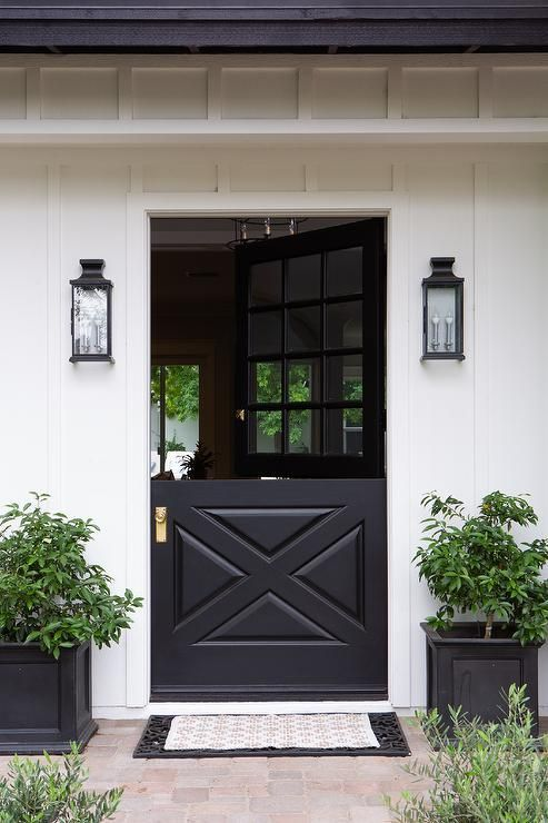 Carriage Lanterns Are Mounted To A White House On Either Side Of A Black Dutch Front Door Fitted With Dutch Doors Exterior House Exterior White Exterior Houses
