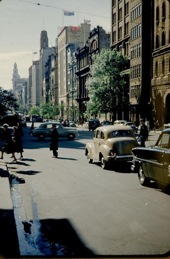 View of Collins Street, looking east from a position to the west of Elizabeth and Queen Streets, near Market Street, Melbourne. The scene shows traffic, pedestrians, the Commercial Bank of Australia, an FJ Holden sedan, and a W-class tram in the background, 1960.  This photograph was taken as a snapshot in 1960, when the photographer came down from Brisbane to visit Melbourne by car and stayed at the Oriental Hotel for holiday. Photographer:	Ms Judith Doig, Brisbane, Queensland, Australia