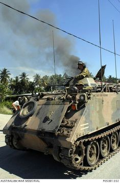 Australian troops travelling in an M113 armoured personnel carrier (APC), provide protection for East Timorese firefighters, the Bombeiros, as they attempt to put out a major fire lit by fueding ...