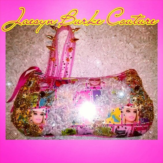 This clutchbag is made of a Barbie-print stretch jersey, embellished with multi-colored Swarovski crystals, Gold and White sequined embroidered, and jet bead flowers, clear oversized jewels, and a Pink satin handle with crystals and gold metal spikes. Barbie Pink sequin mesh in the back, and Pink satin lining. Please allow 3-4 weeks for delivery.