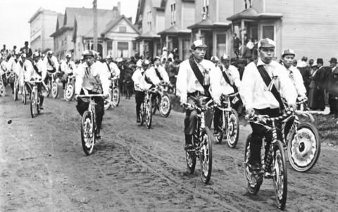 Japanese men in mourning sashes ride bicycles to the memorial service for King Edward VII, May 20, 1910