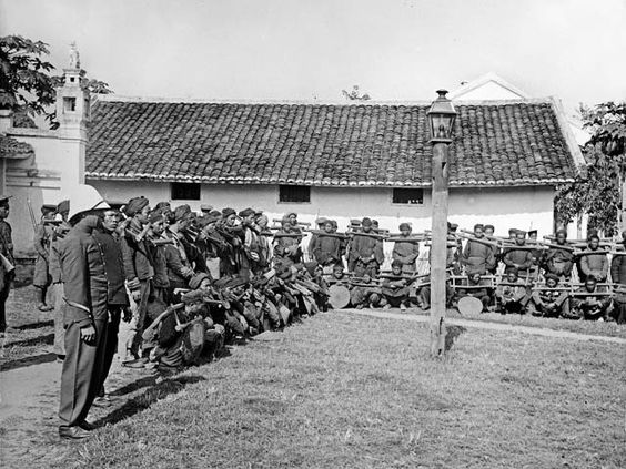 Vietnamese prisoners, held in bamboo restraints stand before their French guard and other Vietnamese onlookers in 1902. [Getty images 557535...