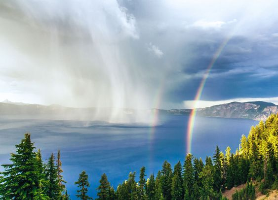 Crater Lake Storm at Sunset: A thunderstorm swirls across the water at Crater Lake National Park, as the setting sun creates a rare double rainbow. Taken from Rim Village, approximately 1,000 feet above the lake's surface, providing a straight-on vantage point of the storm.