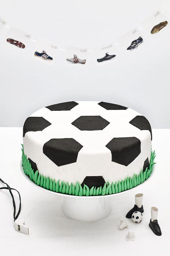 joli gâteau d'anniversaire garçon recouvert de pâte à sucré façon ballon de foot aux bords pelouse en pâte à sucre