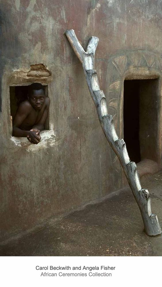 Africa   A child leans out of the window.  A ladder is leaning on the wall.  Kassena, Togo.   ©Carol Beckwith and Angela Fisher