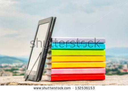 Stack of colorful books with electronic book reader against blue sky - stock photo