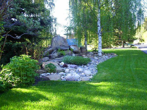 A slight berm topped with a rock garden and a few plants for Landscape berm design