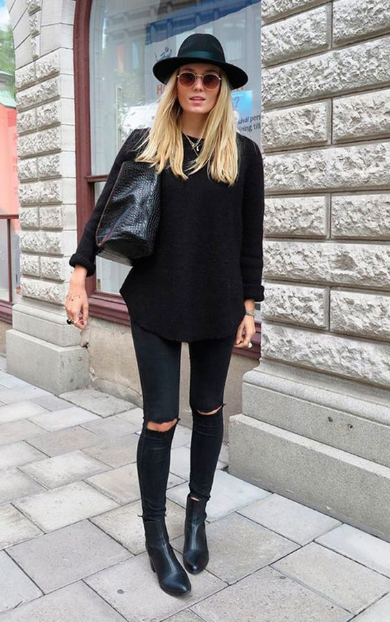 Street style look total black com chapéu, blusa calça rasgada e botas.: