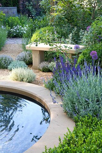 Seating area around pond in modern Mediterranean style garden