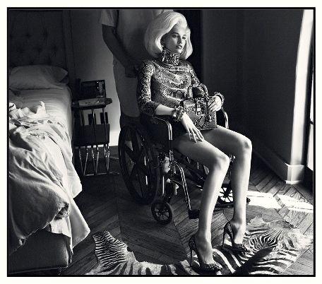 Pubblicità regresso- La fotografia colpisce come un pugno nello stomaco e lascia disorientati. Su una sedia a rotelle, in una improbabile stanza d'ospedale o clinica di lusso, è seduta una donna che, a prima vista, dir...