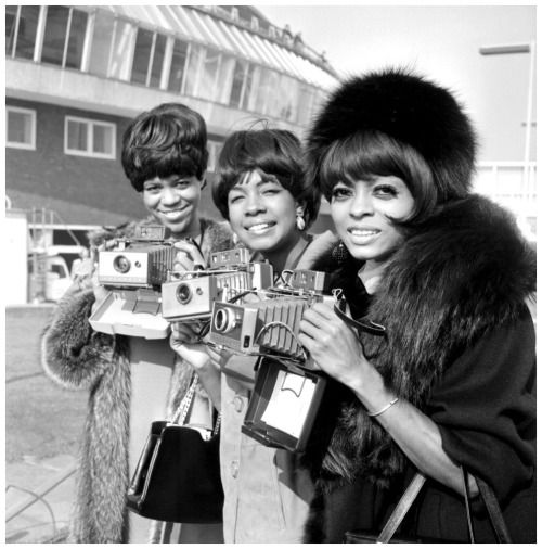 "The Supremes (left to right, Florence Ballard, Mary Wilson and DIana Ross) pose with their cameras as they arrive at London Airport,"" Oct. 5, 1965"