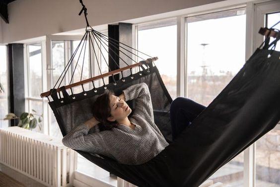 una chica durmiendo sobre una hamaca en el interior de una casa