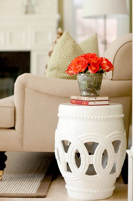 absolutely love this garden stool side table. Click link to view whole room  i also love how the coral of the flowers looks against the white of the table