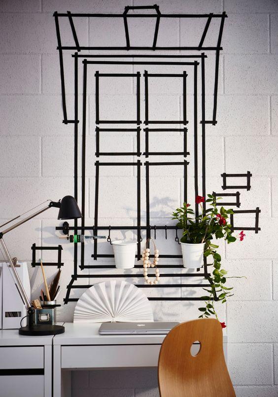 Fita-cola preta em forma de janela colada numa parede Que vista! Revitalize uma parede aborrecida com um pouco de fita decorativa. Sim, ouviu bem! Pegue num rolo de fita-cola e crie a janela com que sempre sonhou.