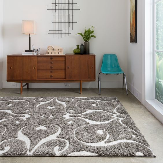 Add the finishing touch to a room with this contemporary shag rug. The durable polypropylene rug features a one-inch pile in varying heights, and an abstract design in charcoal gray, brown, and ivory which will flatter almost any room.: